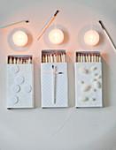 Weiß verzierte Streichholzschachtel, Teelichter und abgebrannte Streichhölzer