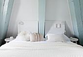Weißes Doppelbett im Schlafzimmer mit hellblauen Balken