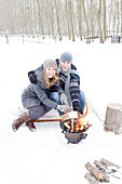 Couple warming hands on brazier in snowy landscape