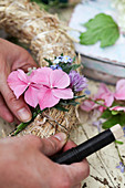 Tying hydrangea florets, forget-me-nots and chive flowers onto straw wreath
