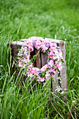 Wreath of hydrangea florets, forget-me-nots and chive flowers on wooden crate in meadow