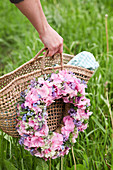 Wreath of hydrangea florets, forget-me-nots and chive flowers on shopping basket