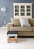 Recycling-Hocker vor beigem Sofa im Wohnzimmer mit blau-grauer Wand