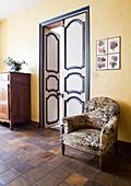 Geblümter Sessel an gelber Wand neben bemalter Flügeltür
