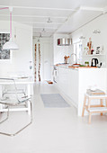 White, open-plan kitchen with white floor and dining area