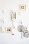 Pictures and embroidering frames hung from stylised twig-shaped hooks