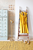 Yellow dress hung from ladder next to pale blue chest of drawers