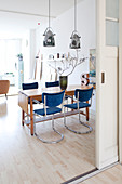 Blue cantilever chairs around old wooden table in vintage-style dining room