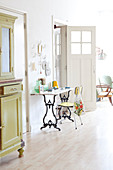 Table on sewing machine base in light-flooded interior