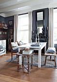 Weißer Esstisch mit Holzbank und Stühlen im Zimmer mit grauen Wänden