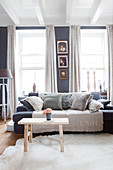 Sofa with scatter cushions and wooden bench used as coffee table in living room with grey walls
