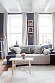 Sofa mit Kissen und Holzbank als Couchtisch im Wohnzimmer mit grauer Wand