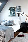 Motto and decorative letters on wall above double bed with scatter cushions