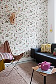 Black couch, classic chair and stylised hunting trophy on patterned wallpaper