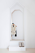 Clothing hung on white door and shoes on step