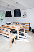 Wooden table and benches on cowhide rug below black pendant lamps