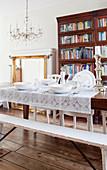 Weißes Gedeck mit Spitzendecke auf Holztisch vor Bücherschrank