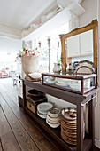 Crockery stacked on sideboard shelves with gilt-framed mirror on top