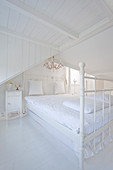 Double bed in white, shabby-chic, attic bedroom