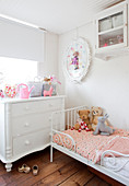 White chest of drawers and soft toys on dainty bed in child's bedroom