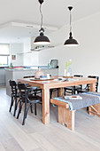 Solid wooden dining table with matching bench and black chairs in front of U-shaped kitchen counter