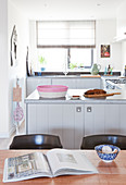 Dining table in front of U-shaped kitchen counter