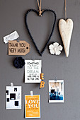 Heart-shaped decorations and postcards with mottoes on grey wall