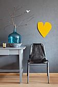 Vintage Stuhl, türkisfarbene Ballonflasche mit Zweig auf Schreibtisch und gelbes Herz an grauer Wand
