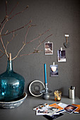 Branch in turquoise demijohn on desk against grey wall