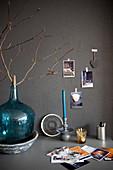Türkisfarbene Ballonflasche mit Zweig auf Schreibtisch vor grauer Wand