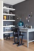Schreibtisch mit Stuhl und Wandregal im Arbeitszimmer mit dunklen Wänden