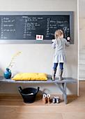 Mädchen auf grauer Holzbank stehend zeichnet an Kreidetafel