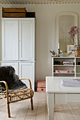 Rattan chair with fur in a white living room in shabby chic style