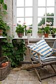 Alter Klappstuhl vorm Sprossenfenster mit Geranien auf der Fensterbank