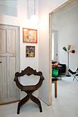 Alter Scherenstuhl vorm Durchgang zum Wohnzimmer mit weißem Dielenboden