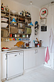 Shelf with dishes in a simple kitchen with a white floor