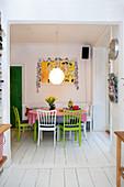 Grüne Sprossenstühle und Bank am Esstisch auf weißem Dielenboden