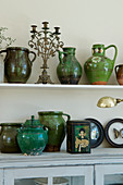 Collection of old clay jugs in shades of green and junk as decoration