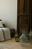 Collection of wine jugs on the floor in front of an old door as decoration