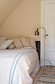Floor lamp next to the bed with old bed linen under the slope
