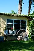 Trödel vorm Schopf mit Sprossenfenster im sommerlichen Garten