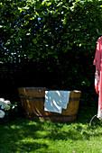 Badewanne aus Holz auf der Wiese im sommerlichen Garten