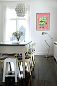 Metal chairs and stools on the old wooden table in the dining room with dark wooden floor