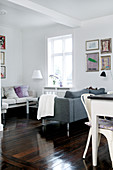 Sofa with back to the dining table as a room divider in the multifunctional living room