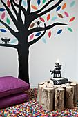 Auf die Wand gemalter Baum und Beistelltisch aus Brennholz