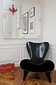 Modern black designer armchair in front of a wall with wainscotting and mirrors