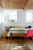 Gestreifte Tischdecke überm Tisch mit pinkem Stuhl und gelber Bank im Esszimmer