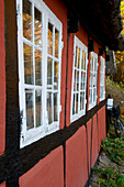 Red half-timbered house with lattice windows in autumn