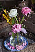 Ranunculus, hyacinths, Australian waxflowers and mimosa flowers in glass vase