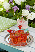 Strawberries on rims of glasses of strawberry squash in front of vase of flowers